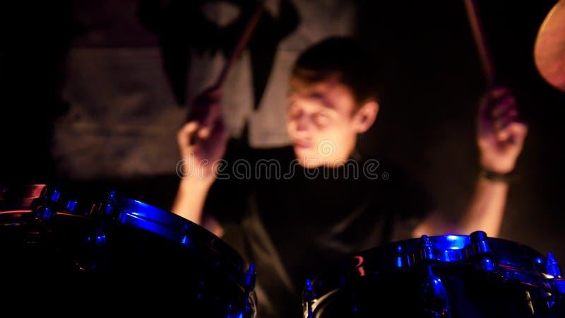 Frau, die Gesangschüssel und Gesang, in der purpurroten und blauen Beleuchtung spielt Ein Mann, der Trommeln auf Stadium spielt D stockfotos