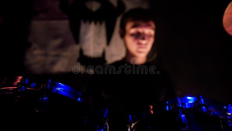 Frau, die Gesangschüssel und Gesang, in der purpurroten und blauen Beleuchtung spielt Ein Mann, der Trommeln auf Stadium spielt T stockbilder