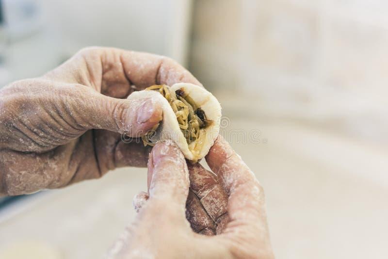 Frau, die geschmackvolle Mehlklöße in der Küche macht lizenzfreie stockfotos