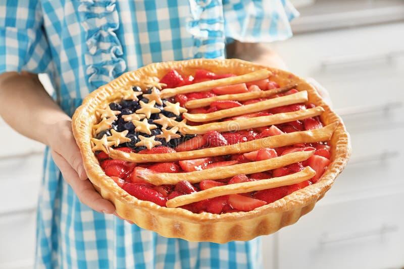 Frau, die geschmackvolle Torte der amerikanischen Flagge hält, lizenzfreies stockbild