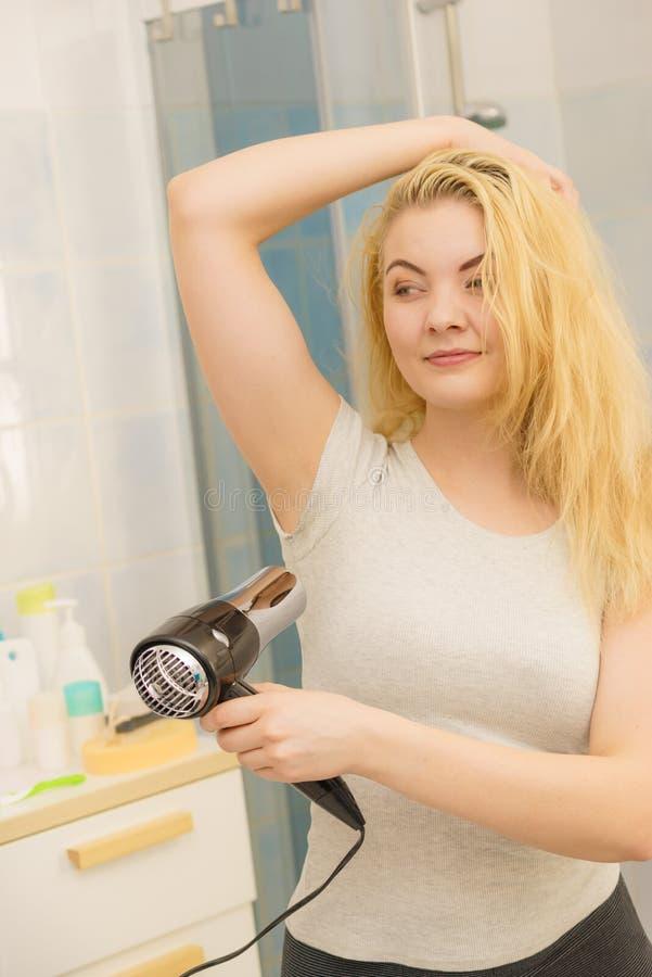 Frau, die geschwitzte Flecke unter Verwendung des Haartrockners trocknet lizenzfreie stockfotografie