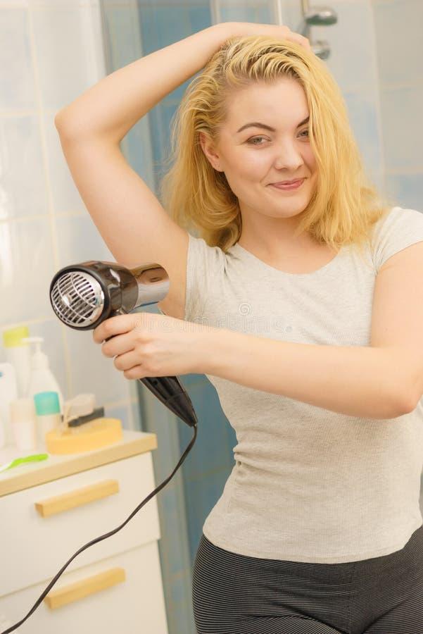 Frau, die geschwitzte Flecke unter Verwendung des Haartrockners trocknet lizenzfreie stockfotos
