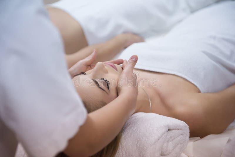 Frau, die Gesicht und Kopfmassage im Badekurortsalon erhält stockfotos
