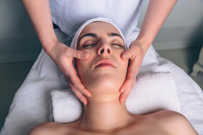 Frau, die Gesichtsbehandlung auf klinischer Mitte bekommt lizenzfreies stockbild