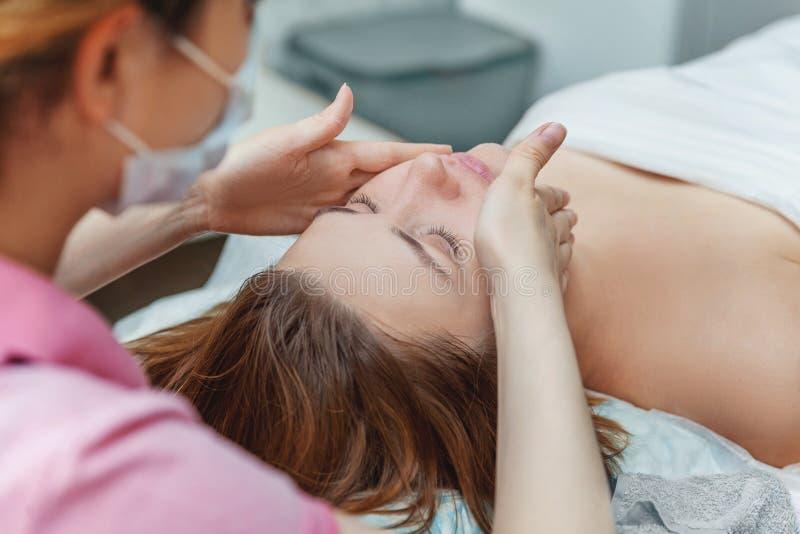 Frau, die Gesichtsbehandlung mit weißer Ernährungscreme im Badekurortsalon erhält lizenzfreie stockfotos