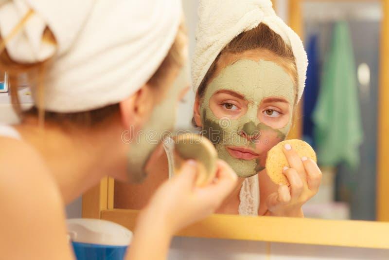 Frau, die Gesichtslehmschlammmaske im Badezimmer entfernt stockfoto