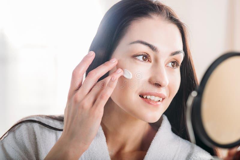 Frau, die Gesichtssahne aufträgt lizenzfreie stockfotografie