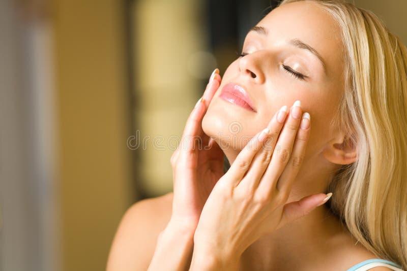 Frau, die Gesichtssahne aufträgt stockfotografie
