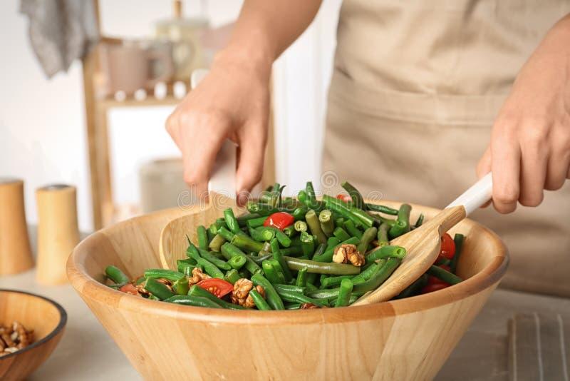 Frau, die gesunden Salat mit grüner Bohne zubereitet stockfotografie
