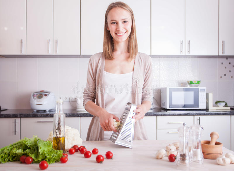 Frau, die gesundes Lebensmittel in der Küche macht lizenzfreie stockfotos