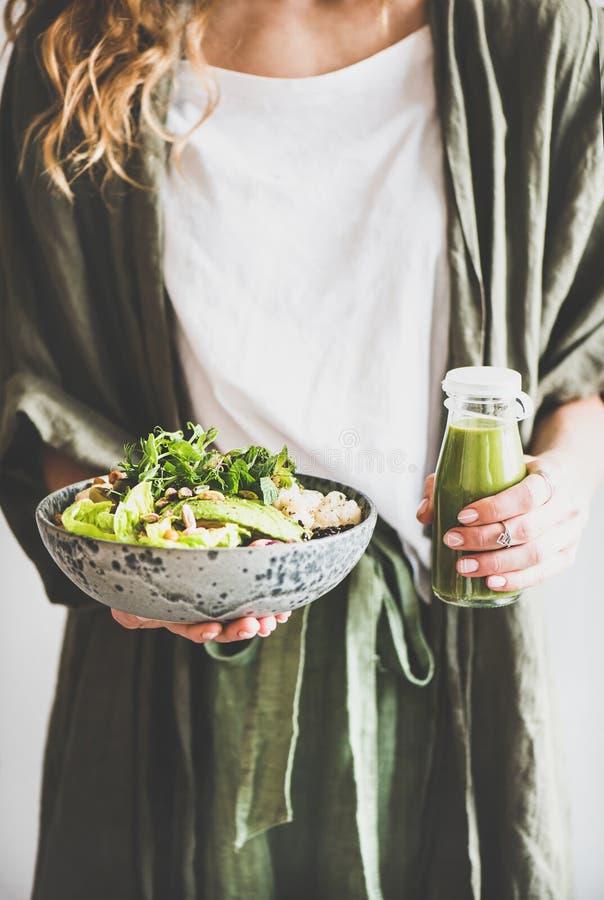 Frau, die gesundes superbowl und Smoothie des strengen Vegetariers in den Händen hält stockbild