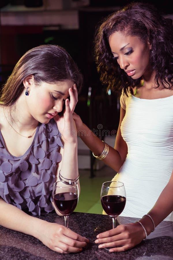 Frau, die Getränke hat und ihren deprimierten Freund tröstet lizenzfreies stockbild