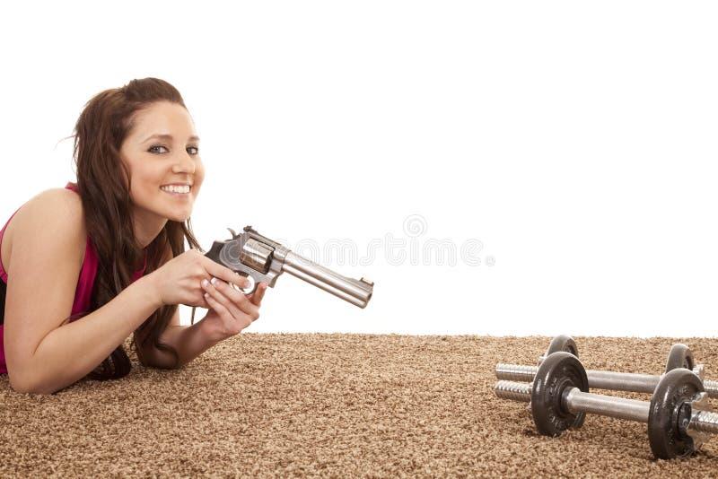 Frau, die Gewehr auf Gewichtlächeln zeigt stockbilder