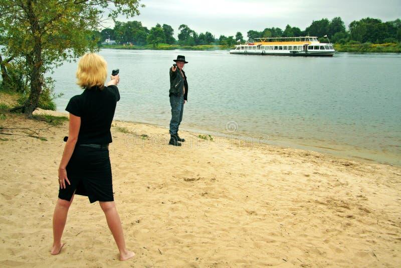 Frau, die Gewehr auf Mann zeigt stockfotos