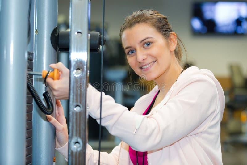 Frau, die Gewichte auf Turnhallenmaschine hinzufügt lizenzfreie stockbilder