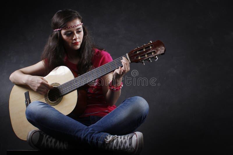 Frau, die Gitarre spielt lizenzfreie stockbilder