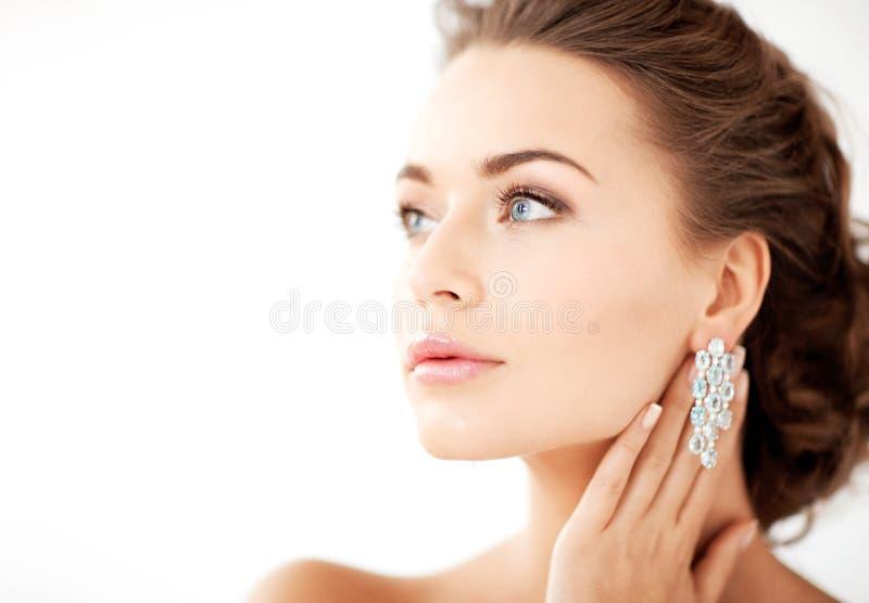 Frau, die glänzende Diamantohrringe trägt lizenzfreie stockfotos