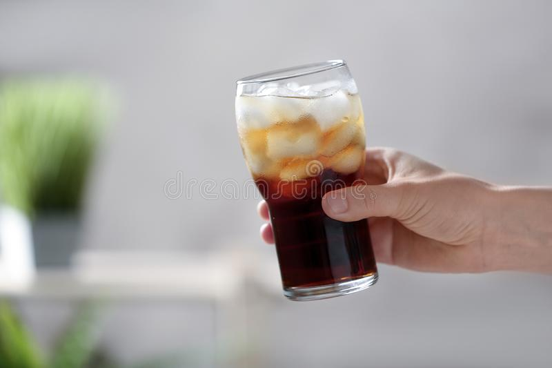 Frau, die Glas Kolabaum mit Eis auf unscharfem Hintergrund, Nahaufnahme h?lt stockfotos