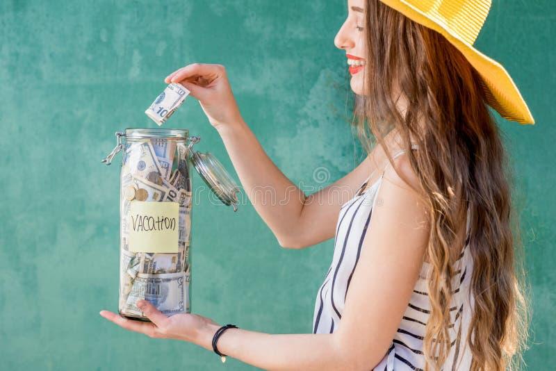 Frau, die Glas voll von den Geldeinsparungen für Sommerferien hält lizenzfreies stockfoto