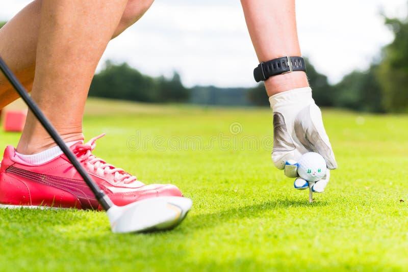 Frau, die Golfball auf T-Stück, Nahaufnahme setzt lizenzfreie stockbilder