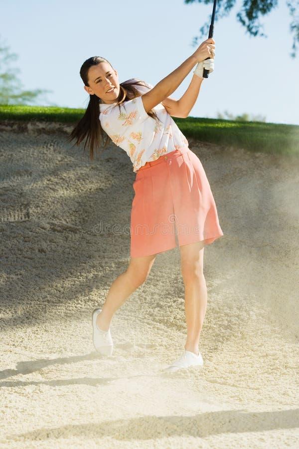 Frau, die Golfball aus einem Sandfang heraus schlägt stockbild