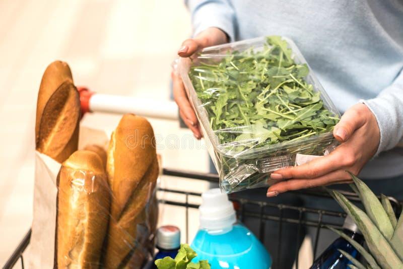 Frau, die grüne Blattgemüse im Lebensmittelgeschäft wählt lizenzfreie stockfotografie