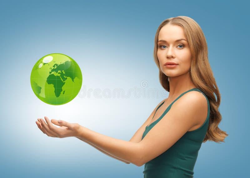 Frau, die grüne Kugel auf ihren Händen hält lizenzfreie stockfotos