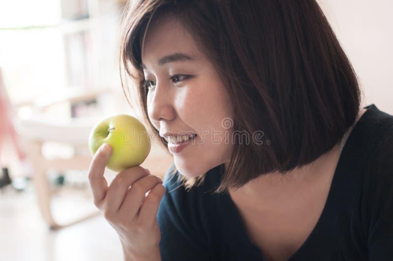 Frau, die grünen Apfel mit dem glücklichen Lächeln hält lizenzfreies stockfoto