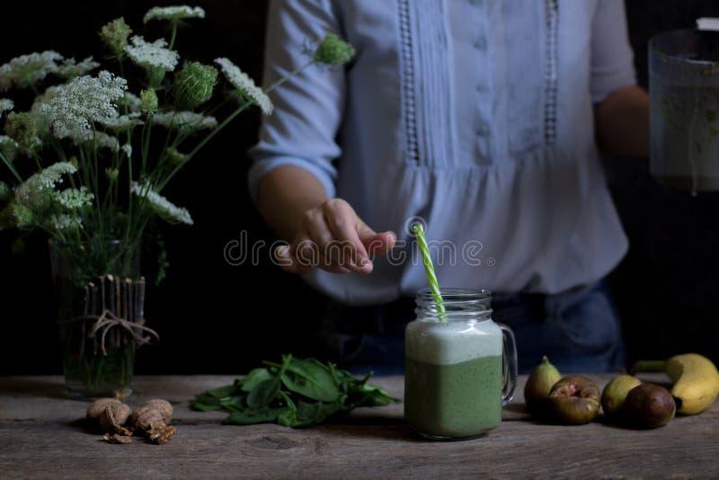 Frau, die grünen und weißen Smoothie mit Feigen, Banane, waln zubereitet lizenzfreie stockbilder