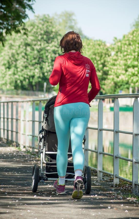 Frau, die in Grenzkanal mit Buggy läuft stockbild