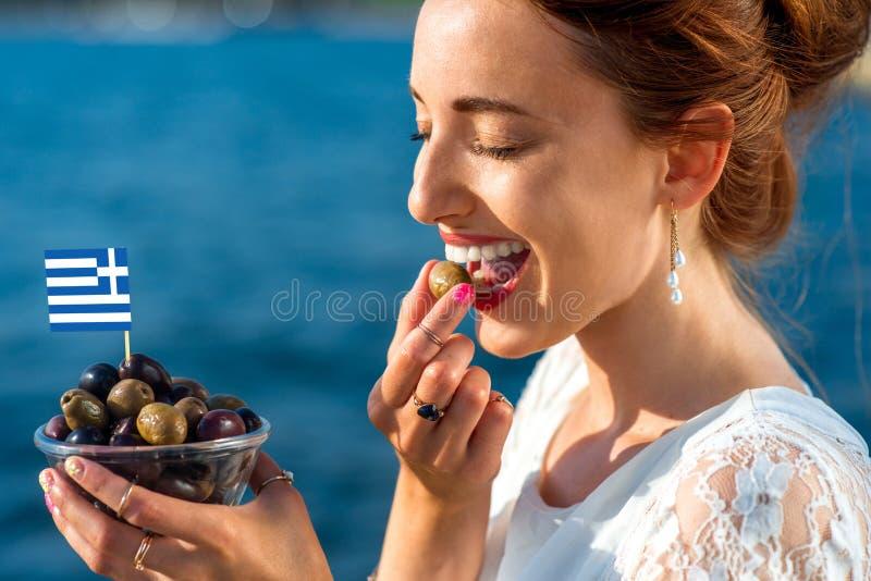 Frau, die griechische Oliven isst stockfoto
