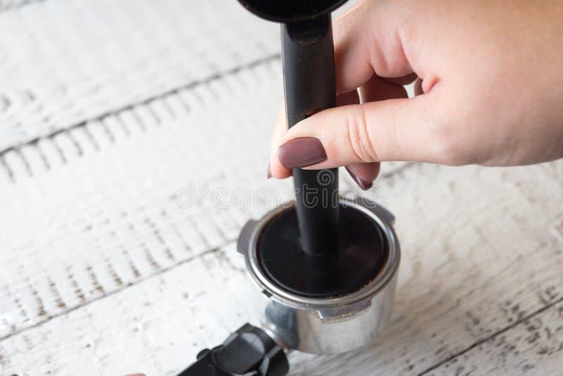 Frau, die grinded Kaffee in einem Gruppenanführer einer Kaffeemaschine bedrängt, um einen Morgenespresso zu machen Frühstück und  stockfotos