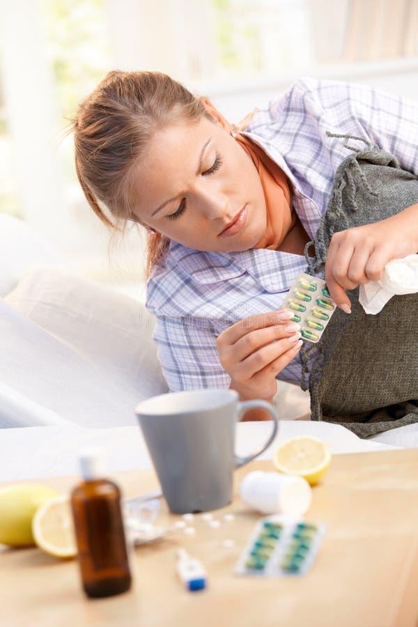 Frau, die Grippe hat, Medizin zu nehmen im Bett lizenzfreies stockbild