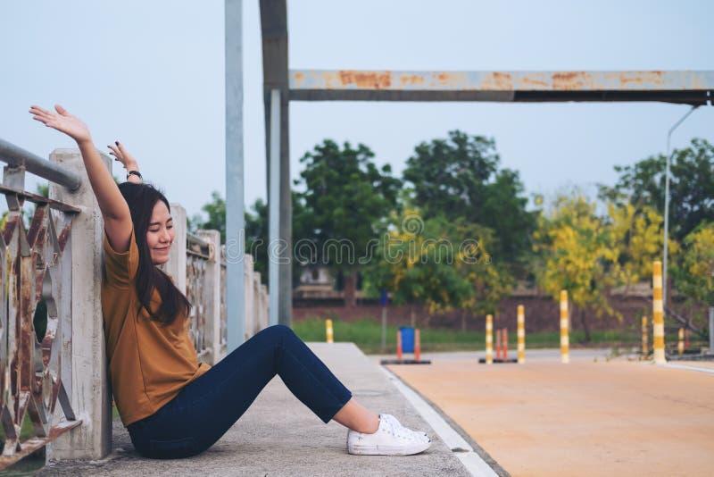 Frau, die Hände auf der Brücke anhebt stockfoto
