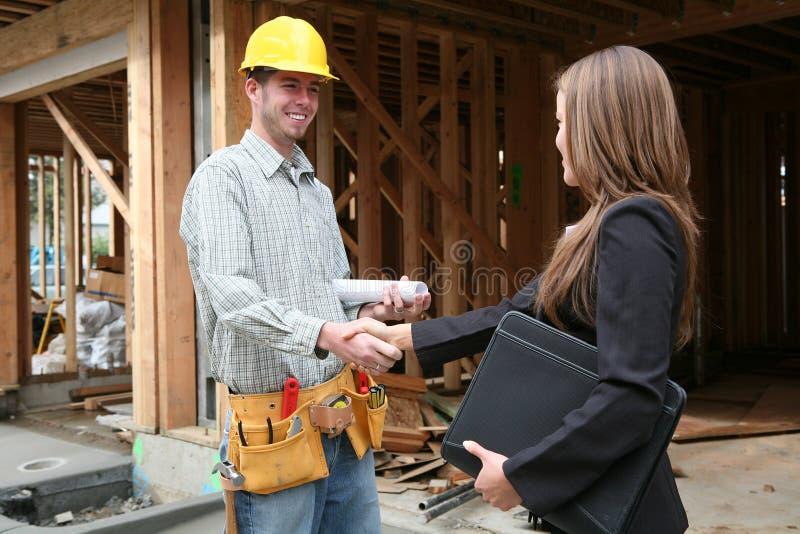 Frau, die Hände mit Aufbau-Mann rüttelt stockfoto
