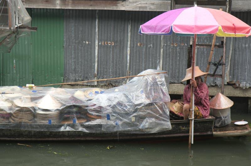 Frau, die Hüte an sich hin- und herbewegendem Markt Dumnoen Saduak verkauft stockfotos