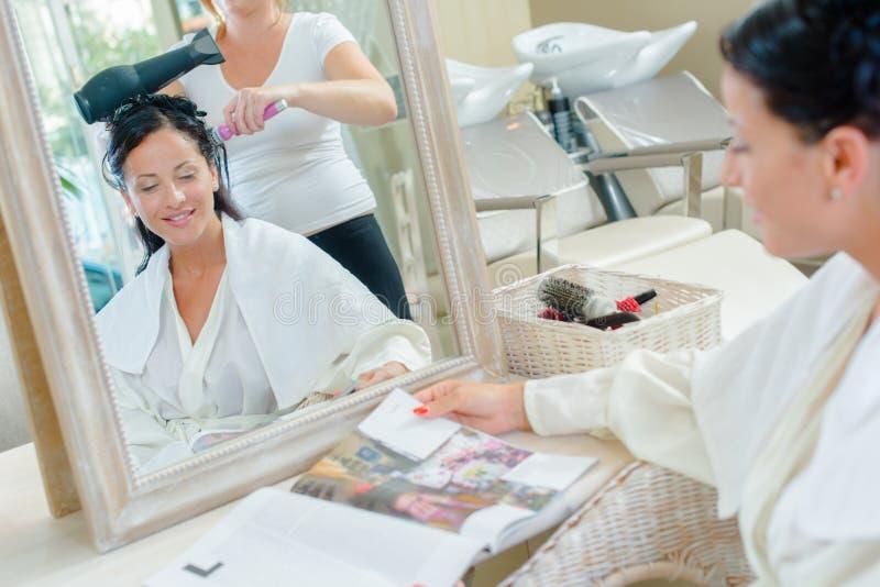 Frau, die Haar trocknen lässt, Zeitschrift lesend lizenzfreies stockbild