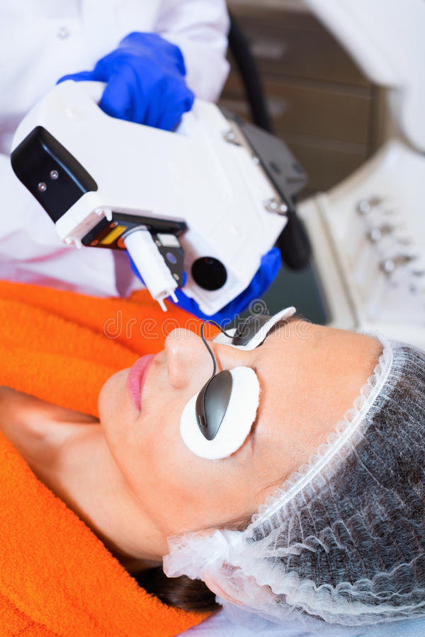 Frau, die Haar vom Gesicht mit Laser entfernt lizenzfreie stockbilder