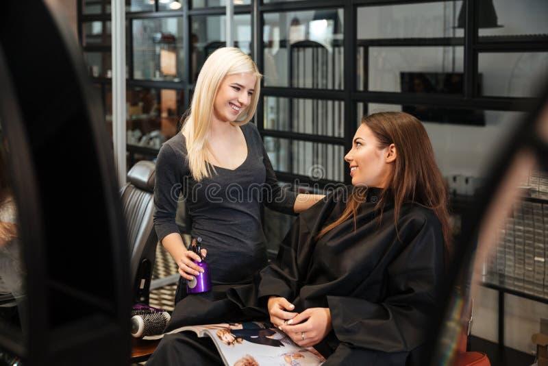 Frau, die Haarschnitt mit ihrem Friseur im Frisörsalon bespricht stockbild