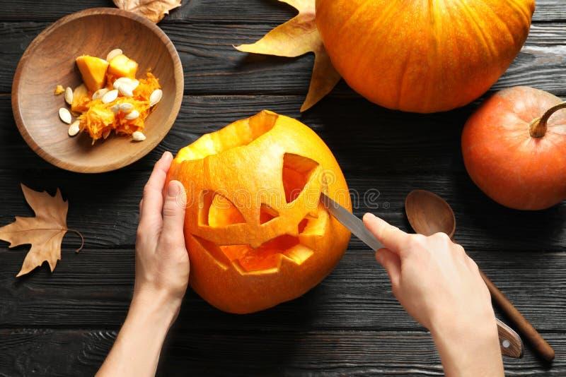 Frau, die Halloween-Kürbiskopf-Steckfassungslaterne auf Holztisch schnitzt lizenzfreie stockfotos