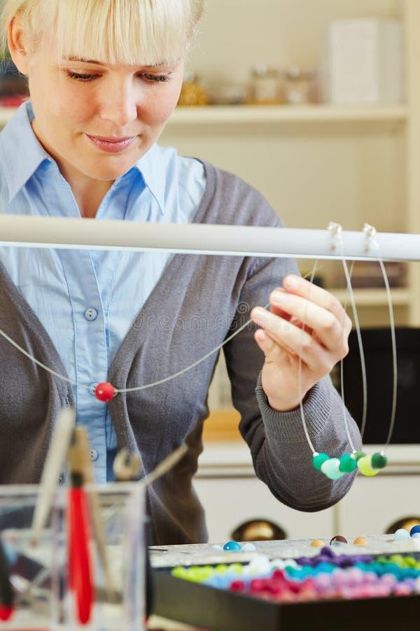 Frau, die Halskette in der Werkstatt herstellt stockfoto