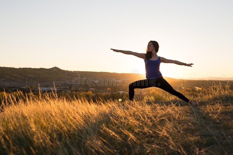 Frau, die Haltung des Yogakriegers II während des Sonnenuntergangs tut lizenzfreie stockfotos