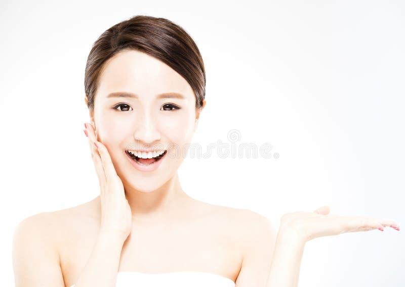 Frau, die an Hand Schönheitsprodukt zeigt stockfotos