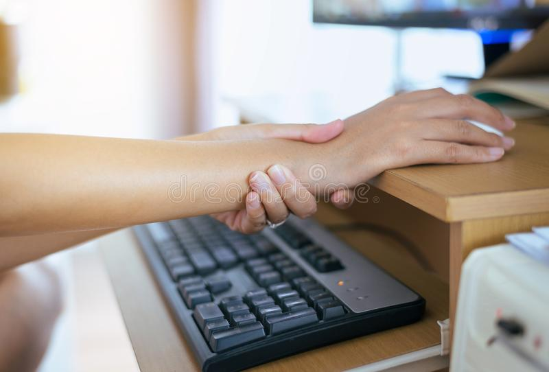 Frau, die Handgelenk- oder Handschmerz, weibliches Gefühl erschöpft und schmerzlich hat, weil, Maus anklickend und mit Computer lizenzfreie stockbilder