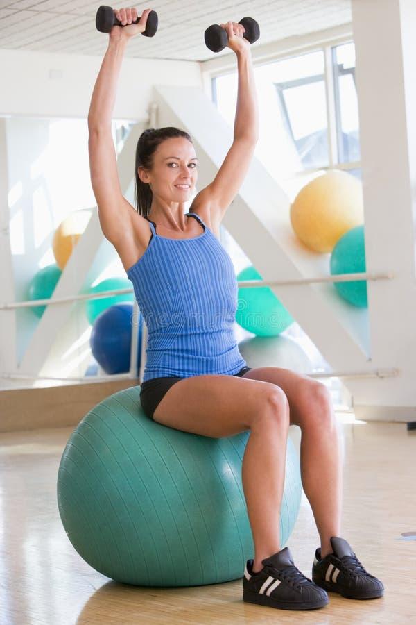 Frau, die Handgewichte auf Schweizer Kugel an der Gymnastik verwendet stockbild