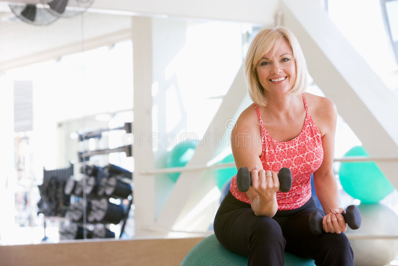 Frau, die Handgewichte auf Schweizer Kugel an der Gymnastik verwendet stockfotos