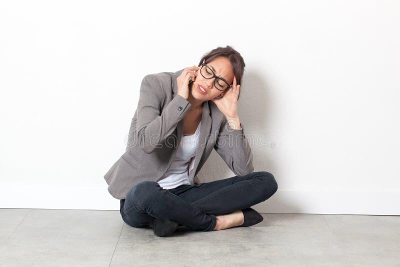 Frau, die am Handy allein sitzt auf Büroboden über spärlichem spricht stockfotos