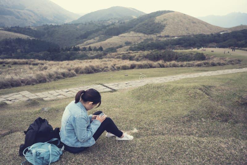 Frau, die Handy bei der Entspannung mit Bergblick verwendet stockfotografie
