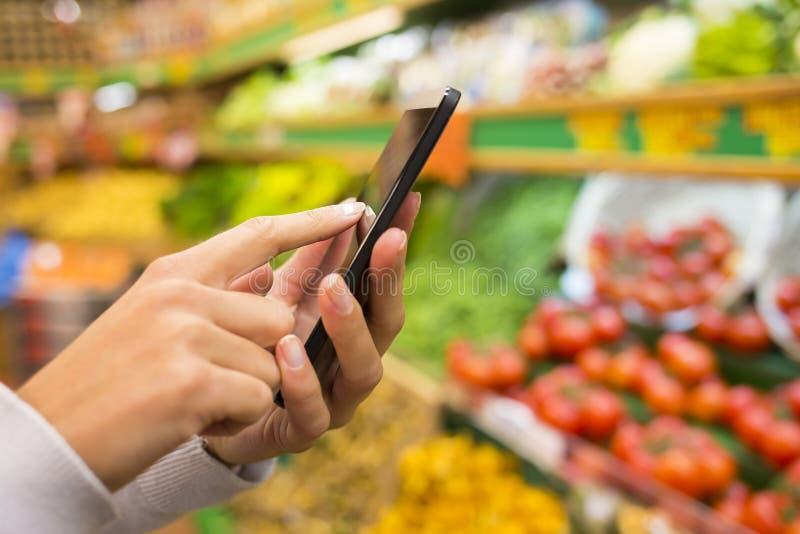 Frau, die Handy beim Einkauf im Supermarkt verwendet stockfotografie