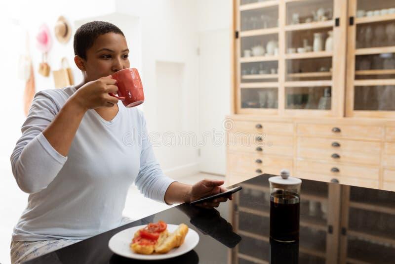 Frau, die Handy beim Trinken des Kaffees auf einem Speisetische verwendet lizenzfreies stockbild